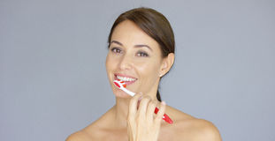 Smiling pretty young woman brushing her teeth Royalty Free Stock Photography