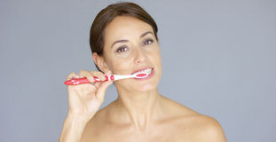 Smiling pretty young woman brushing her teeth royalty free stock photo