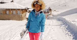 Smiling pretty young woman carrying a snowboard Royalty Free Stock Images