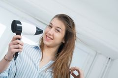 Pretty young woman is drying her hair. Smiling pretty young woman is drying her hair Royalty Free Stock Image