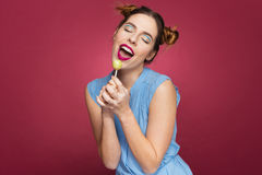 Smiling pretty young woman holding lollipop and singing. Over pink background stock photography