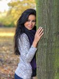 Smiling Pretty Young Woman Leaning on Tree Trunk Royalty Free Stock Images