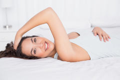 Smiling pretty young woman lying in bed Royalty Free Stock Photography