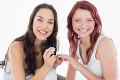 Smiling pretty young woman painting friends nails Royalty Free Stock Images