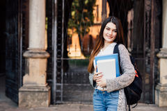 Smiling pretty young woman student with backpack walking outdoors near campus Royalty Free Stock Image