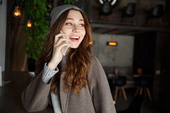 Smiling pretty young woman talking on cell phone in cafe. Smiling pretty young woman in hat and coat talking on cell phone in cafe Stock Images
