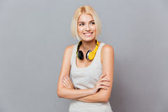 Smiling pretty young woman using headphones standing with arms crossed. Smiling pretty young woman with headphones standing with arms crossed over gray Royalty Free Stock Photography