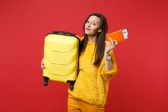 Smiling pretty young woman in yellow fur sweater holding suitcase, passport boarding pass ticket isolated on bright red. Wall background. People sincere stock photography