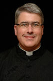 Smiling Priest. Vertical portrait of a priest wearing a black clerical shirt with a white clerical collar against a black background stock photography