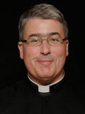 Smiling priest. Portrait of smiling middle-aged priest with clerical collar, black background stock photos