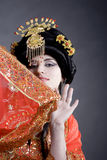 Smiling princess. Asian princess hiding behind her embroidered golden red dress. Wearing a golden crown and having a playful look Stock Photography