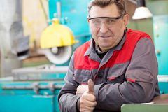 Smiling production senior man worker gesturing OK. Workshop Machinery. Smiling production senior man worker gesturing OK on manufacture surface grinding machine Royalty Free Stock Images