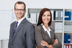 Smiling professional business man and woman. Professional business men and women standing back to back in the office looking at the camera with confident smiles Royalty Free Stock Image