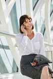 Smiling professional business woman talking on smart phone. Portrait of smiling professional business woman talking on smart phone Royalty Free Stock Photography