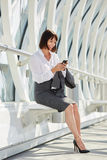 Smiling professional business woman waiting with smart phone. Full body portrait of smiling professional business woman waiting in terminal with smart phone Royalty Free Stock Photos