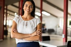 Smiling professional businesswoman in casual, with arms crossed standing in office. Stock Photography