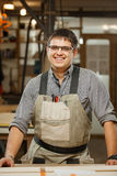 Smiling professional carpenter in gasses and uniform at workshop Stock Image