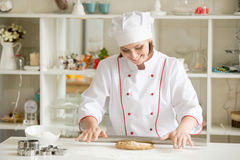 Smiling professional confectioner rolling gingerbread dough Royalty Free Stock Image
