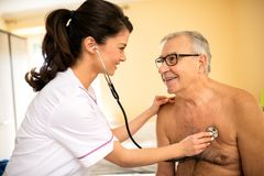 Smiling professional feamle doctor examining senior man with ste. Smiling professional feamle doctor examining senior men with stethoscope at nursing home Stock Images