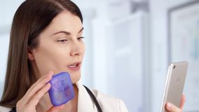 Professional female doctor in hospital room talking on phone with patient. Woman physician at work. Smiling professional female doctor with stethoscope standing stock footage