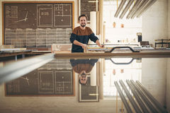 Smiling professional framer in his studio working. Portrait of a positive and professional framer at work in his studio, with tools on his workbench and looking Royalty Free Stock Image