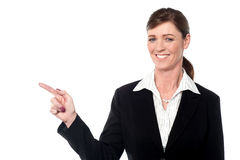 Smiling professional lady pointing away Royalty Free Stock Image