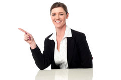 Smiling professional lady pointing away Royalty Free Stock Images