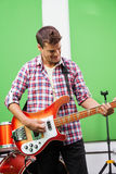 Smiling Professional Playing Guitar In Recording Studio Stock Photography