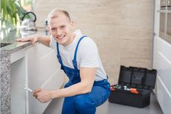 Smiling professional plumber with tools Royalty Free Stock Images