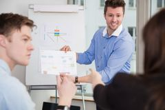 Smiling Professional Showing Chart To Colleagues royalty free stock images