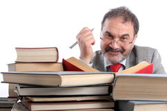 Smiling professor. Single male is sitting behind a pile of books. Looking at camera, smiling. Holding a pen in his hand Stock Images