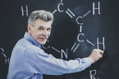 Smiling Professor Explains New Chemistry Topic. Teacher Writes Formula on the Blackboard. Explanation for Students. Educational Concept. Closeup of Sientist royalty free stock image