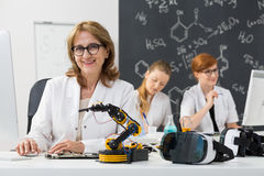 Smiling professor sitting in a classroom Royalty Free Stock Image