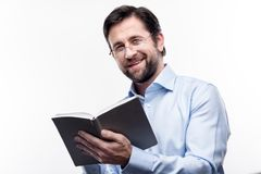 Smiling professor writing in his notebook. Thoroughly organized. Pleasant cheerful professor in eyeglasses writing in his notebook while smiling at the camera stock photography