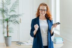 Smiling prosperous ginger female banker makes payment on online servie, waits for important call, holds modern cell phone, looks. Postively at camera, dressed royalty free stock photos