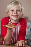Smiling proud boy holding up gingerbread man royalty free stock image