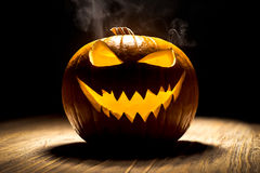 Smiling pumpkin with smoke. At a wooden old table Stock Photography