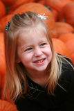 Smiling with Pumpkins. Cute little girl smiling in a pumpkin patch Royalty Free Stock Photos
