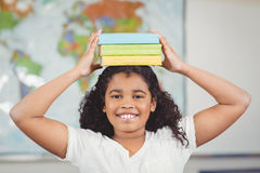 Smiling pupil balancing books on head in a classroom Royalty Free Stock Photography