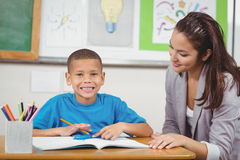 Smiling pupil being helped by teacher. Portrait of smiling pupil being helped by teacher in a classroom Stock Photo
