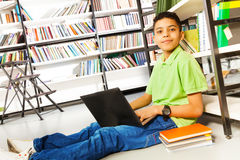 Smiling pupil with books and laptop in library Royalty Free Stock Photos