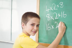 Smiling pupil calculating on chalkboard in a classroom Royalty Free Stock Photos