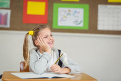 Smiling pupil daydreaming in a classroom Royalty Free Stock Photography
