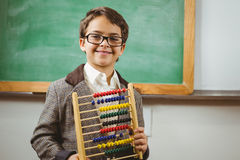 Smiling pupil dressed up as teacher holding abacus Stock Images