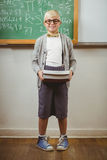 Smiling pupil dressed up as teacher holding books. Portrait of smiling pupil dressed up as teacher holding books in a classroom Stock Image