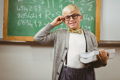 Smiling pupil dressed up as teacher holding books. Portrait of smiling pupil dressed up as teacher holding books in a classroom Royalty Free Stock Images