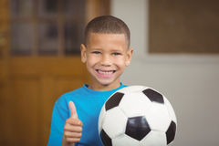 Smiling pupil holding football and doing thumbs up Stock Photography