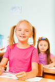 Smiling pupil holds pencil and sits at desk Royalty Free Stock Photography