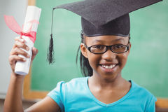 Smiling pupil with mortar board and diploma Stock Photo