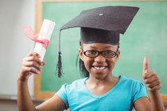 Smiling pupil with mortar board doing thumbs up Royalty Free Stock Photography